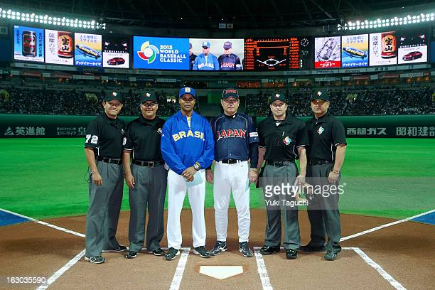Barry Larkin manager of Team Brazil and Koji Yamamoto manager of Team Japan pose for a photo with the umpiring crew before the Pool A Game 1 between...
