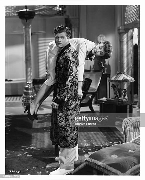 Barry Nelson carrying Laraine Day over his shoulder in a scene from the film 'A Yank On The Burma Road', 1942.