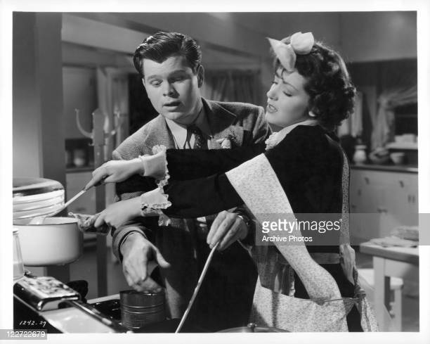 Barry Nelson helps Marsha Hunt prepare dinner in a scene from the film 'The Affairs Of Martha', 1942.
