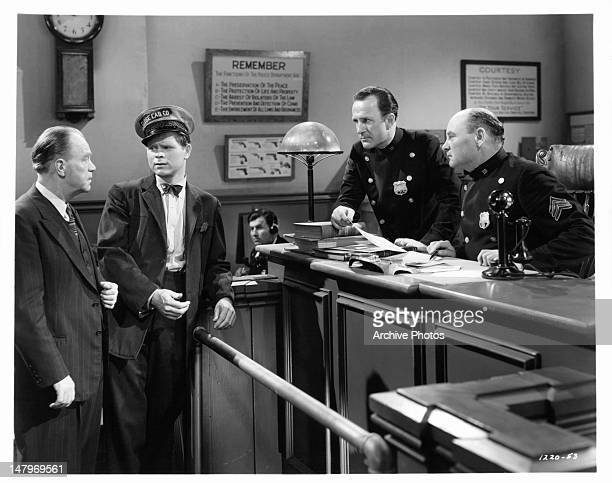Barry Nelson in the middle of group in police station in a scene from the film 'A Yank On The Burma Road' 1942