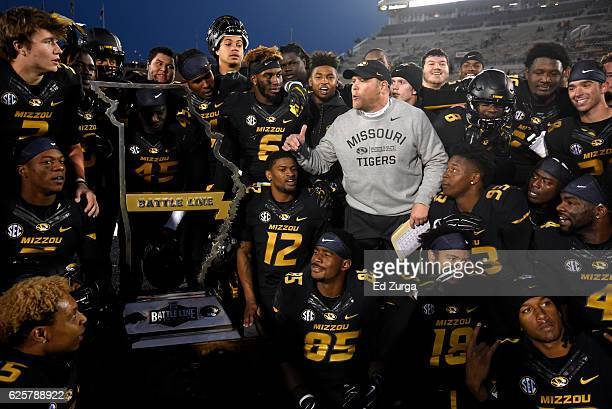 Barry Odom head coach of the Missouri Tigers and his team celebrate with the Battle Line trophy after their 2824 win over the Arkansas Razorbacks at...