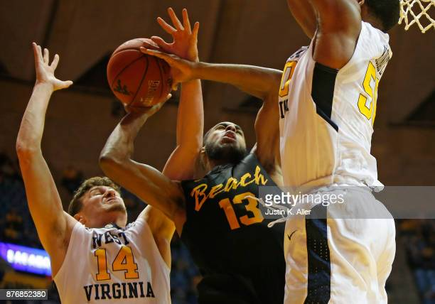 Barry Ogalue of the Long Beach State 49ers battles against Chase Harler and Sagaba Konate of the West Virginia Mountaineers at the WVU Coliseum on...