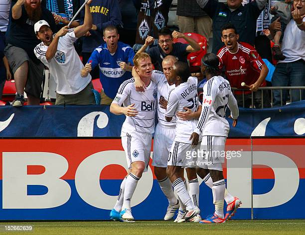 Barry Robson of the Vancouver Whitecaps FC hugs goal scorer Kenny Miller while Dane Richards and Darren Mattocks join the celebration against the...