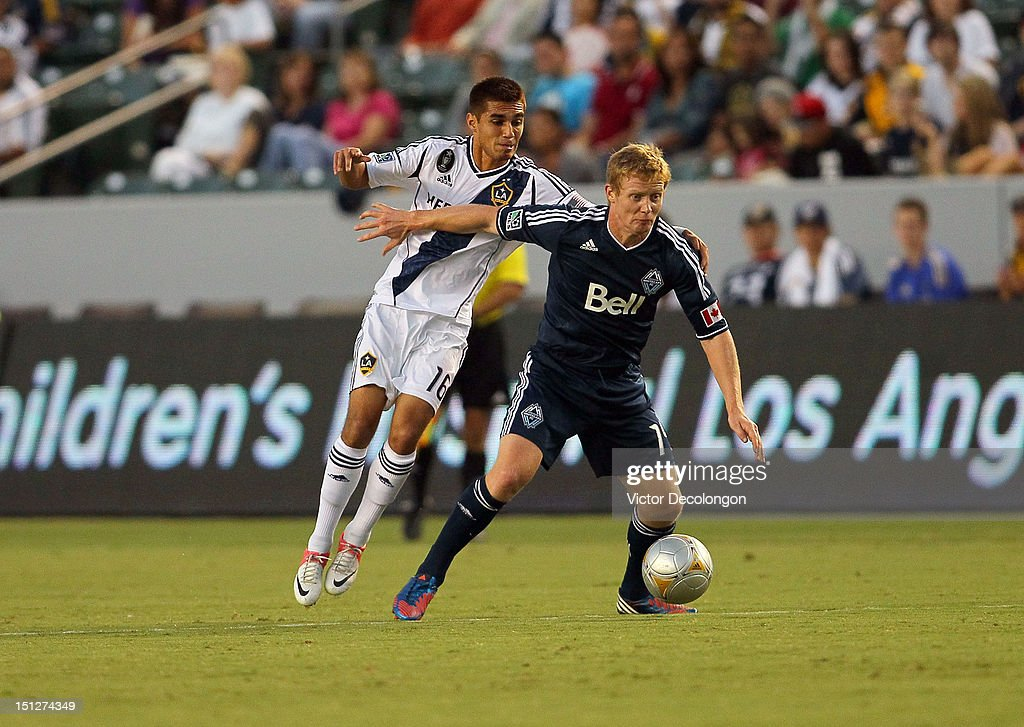 Barry Robson #14 of the Vancouver Whitecaps holds off a challenge from Hector Jimenez #16 of the Los Angeles Galaxy in the first half during the MLS match at The Home Depot Center on September 1, 2012 in Carson, California. The Galaxy defeated the Whitecaps 2-0.