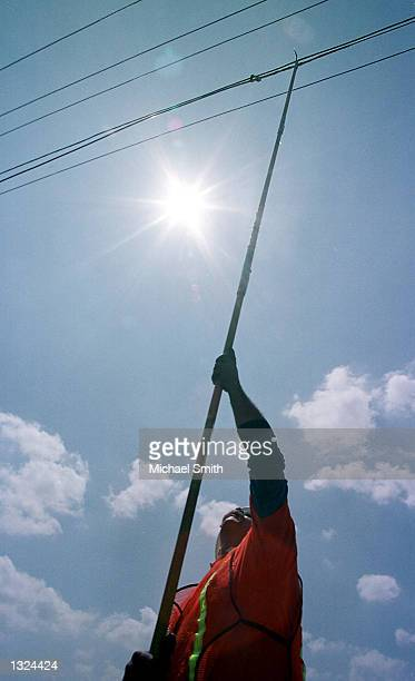 Barry Schmidt guides fiberoptic cable with a pole during aerial installation to telephone poles June 21 2001 in Louisville CO