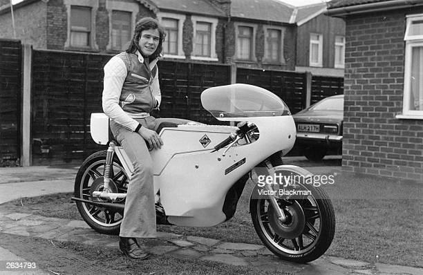 Barry Sheene British champion motorcyclist astride his Formula one Seeley motorcycle on the front path of a domestic property