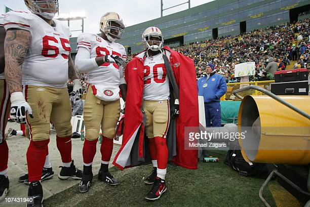 Barry Sims Vernon Davis and Brian Westbrook of the San Francisco 49ers try to keep warm during the game against the Green Bay Packers at Lambeau...