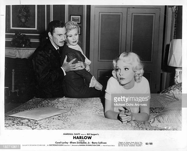 Barry Sullivan holding Ginger Rogers near Carol Lynley who's lying on the bed in a scene from the film 'Harlow' 1965