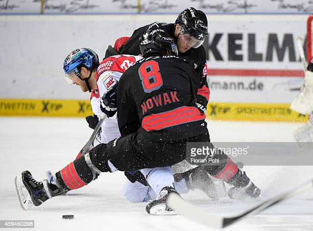 Barry Tallackson of the Eisbaeren Berlin, Marco Nowak and Derek Joslin of the Thomas Sabo Ice Tigers Nuernberg duel during the game between Thomas...