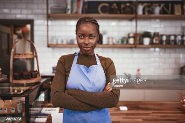 bars an restaurants opening after coronavirus pandemic - african employee behind the counter - owner stock pictures, royalty-free photos & images