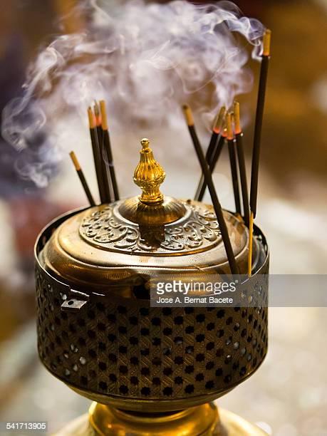 Bars of incense on a former burner of bronze
