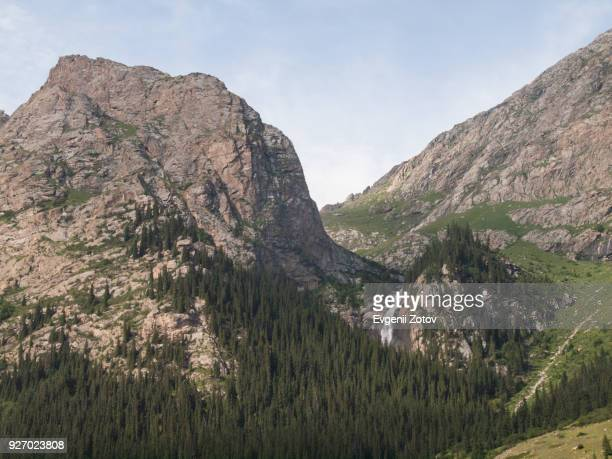 barskoon waterfall in kyrgyzstan - rock overhang stock photos and pictures