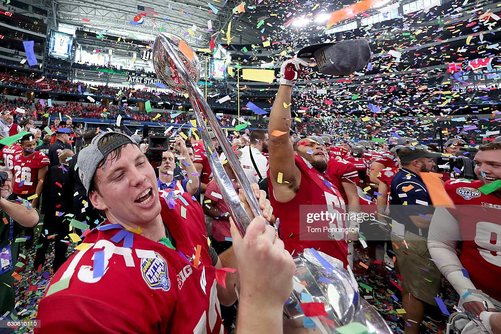Bart Houston #13 of the Wisconsin Badgers celebrates with the trophy after the Wisconsin Badgers beat the Western Michigan Broncos 24-16 in the 81st Goodyear Cotton Bowl Classic at AT&T Stadium on January 2, 2017 in Arlington, Texas.