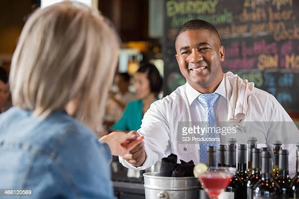 Bartender accepting credit card from customer to pay bar tab