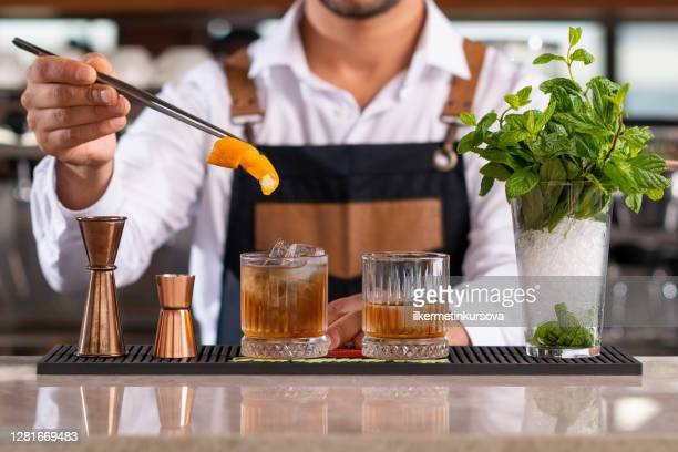 bartender adding lemon peel in a drink - cocktail party stock pictures, royalty-free photos & images