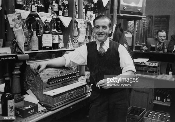 Bartender and a cash till behind the bar of a Liverpool public house Original Publication Picture Post 8995 Liverpool Slums unpub