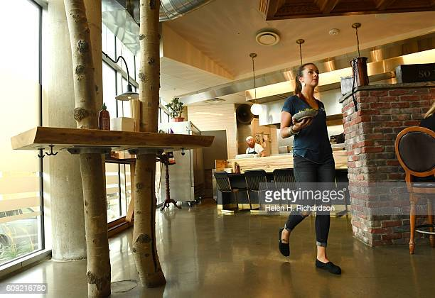 Bartender and waitress Ashley Conner delivers a dish to a patron at There Restaurant on September 16 2016 in Denver Colorado The interior of the...