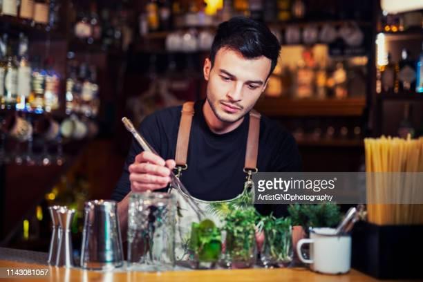 bartender an der bartheke, die grüne frische kräuter für den nächsten cocktail zubereiten. - kombination stock-fotos und bilder