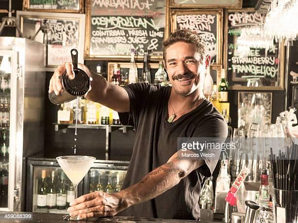 Bartender at counter making cocktails