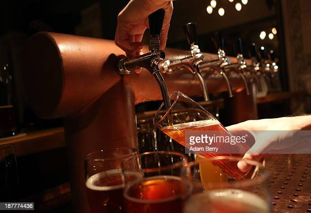 A bartender at Hops Barley brewpub pours a pint of beer on November 12 2013 in Berlin Germany In a country known for centuries for its beer several...