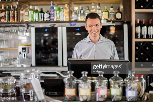 Bartender behing the counter at a bar