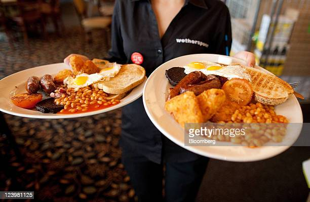 A bartender carries two breakfast plates at The Knights Templar public house operated by JD Wetherspoon Plc in London UK on Wednesday Sept 7 2011 UK...
