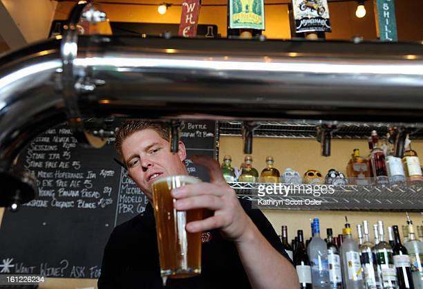 Bartender Chandler Smith serves up a pint of Easy Street at the Lowry Beer Garden at 7577 E. Academy Blvd. In Denver on Saturday, May 26, 2012....