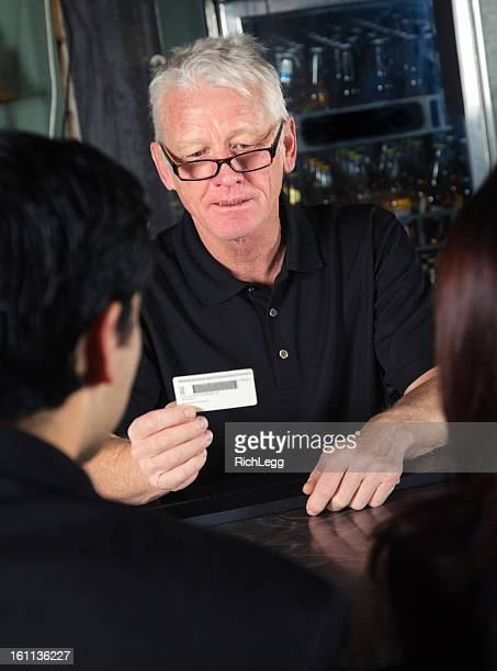 bartender checking id - doorman stock photos and pictures