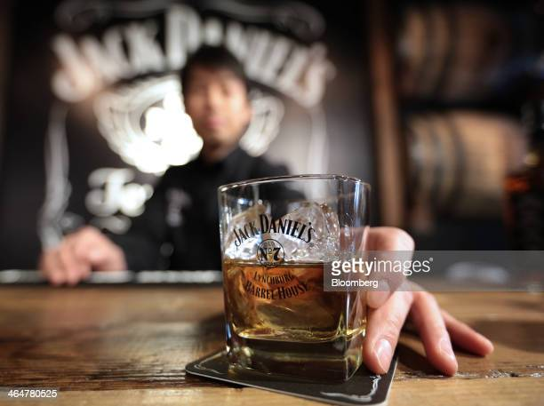 Bartender Chisei Kawaguchi places a glass of Jack Daniel's whiskey on a coaster for an arranged photograph during a media preview of the Jack...