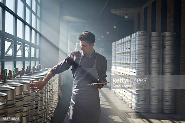 bartender counting beer keg's and using tablet - entrepreneur stock-fotos und bilder