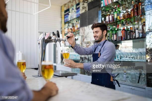 バーテンダーはタップからグラスでビールをファイリング - ビールサーバー ストックフォトと画像