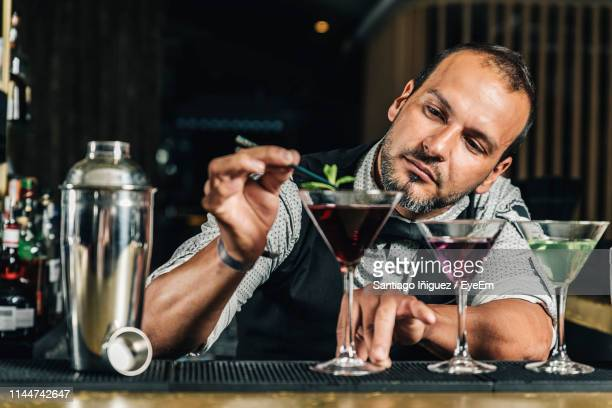 bartender garnishing drink on counter in bar - bartender stock pictures, royalty-free photos & images