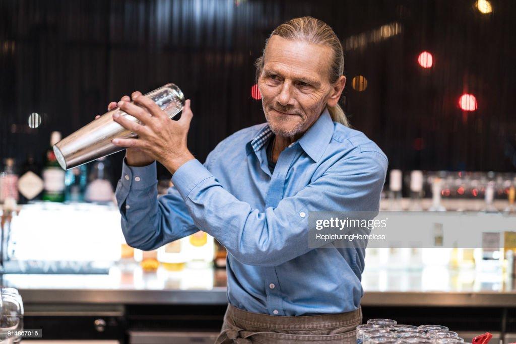 Barmann bereitet ein Getränk mit einem Cocktail-Shaker zu : Stock-Foto