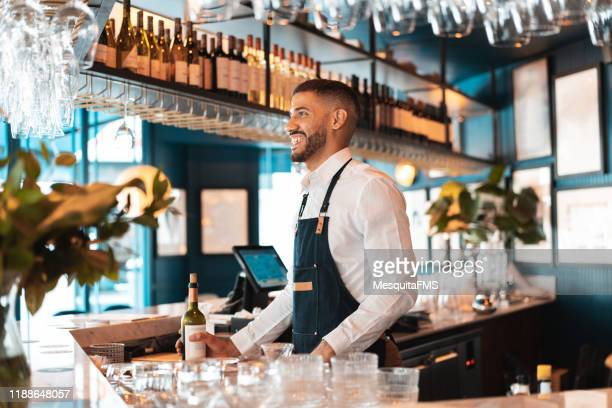 bartender holding a bottle of wine from the bar - bar drink establishment stock pictures, royalty-free photos & images