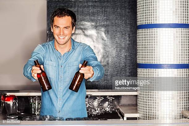 bartender holding beer bottles at counter in nightclub - one man only stock pictures, royalty-free photos & images