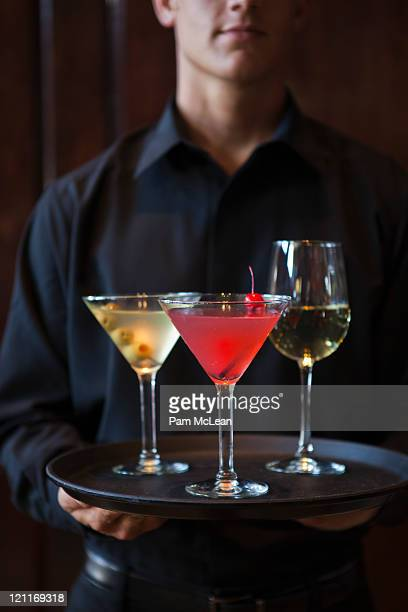 Bartender holding tray of alchaholic beverages