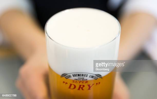 A bartender holds a glass of Asahi Super Dry beer at the Asahi Kanagawa Brewery operated by Asahi Breweries Ltd a unit of Asahi Group Holdings Ltd in...