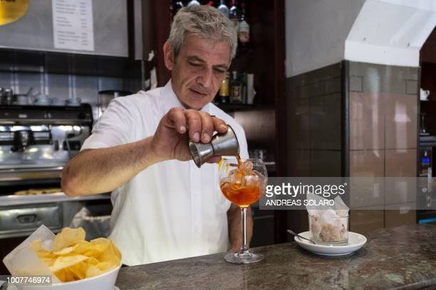 A bartender holds a measuring cup while preparing a Spritz cocktail in a cafe in central Rome on July 17 2018 Aperol is a historical brand which has...