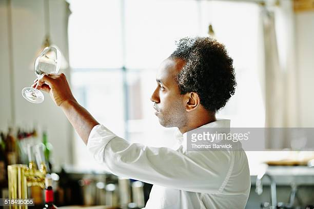 Bartender in restaurant examining wine glass