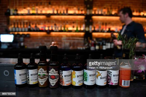 DENVER CO OCTOBER 24 Bartender J Jenson right tends the bar with a row of a variety of bitters used in drinks at the new bar called SneekEazy on...