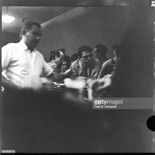 Bartender John Bodner servers drinks at the Cedar Street Tavern New York New York August 19 1959 Over his left arm American theatre director and...