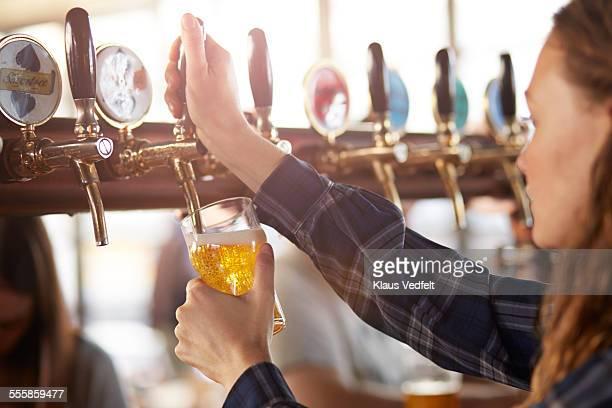 Bartender making cask beer at bar