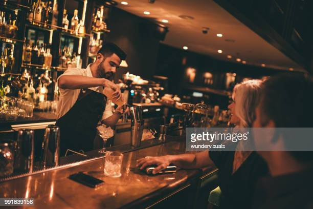bartender making cocktails at retro bar for mature couple - cocktail party stock pictures, royalty-free photos & images