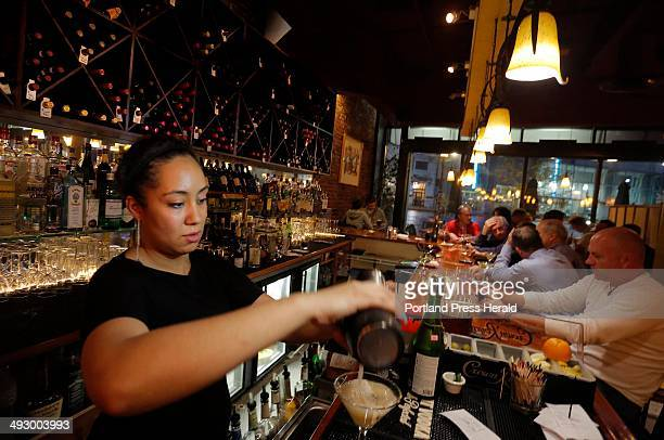 Bartender Mia Houser pours a sparkling bellini one of the speciality drinks at David's in Monument Square Thursday night May 23 2013
