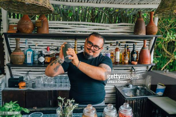 bartender mixing a drink in open air bar - bartender stock pictures, royalty-free photos & images