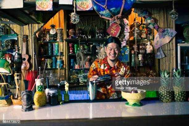 Bartender mixing cocktails and making drinks in a tropical themed restaurant or bar