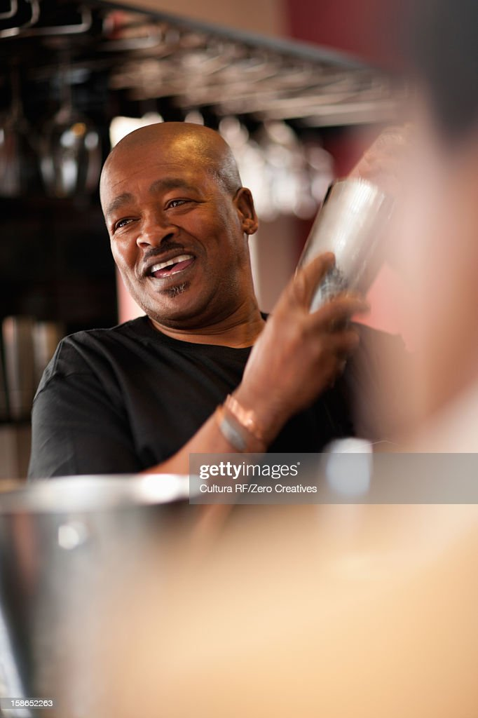 Bartender mixing drinks at bar : Stock Photo