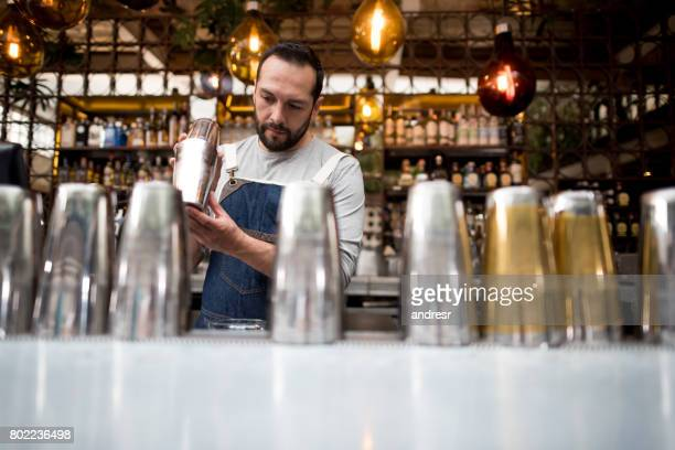 bartender mixing drinks at the bar - food and drink industry stock photos and pictures