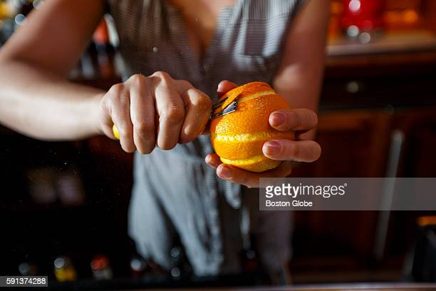 Bartender Naomi Levy peels orange as she makes the drink known as Montenegro Time at the restaurant Capo in Boston on Aug 8 2016