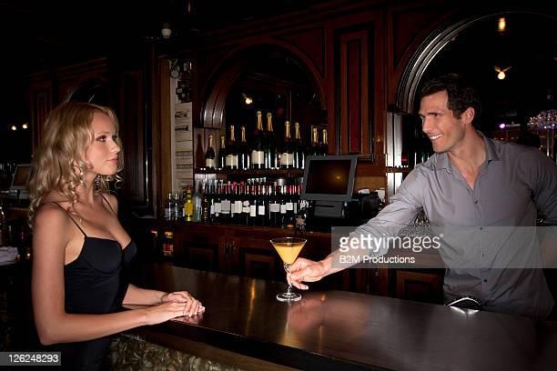 Bartender offering cocktail in baroman in bar